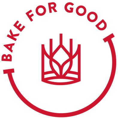 """""""Bake for Good"""" circle logo in red with the words Bake for Good forming an arc of the circle and with the King Arthur Baking Company logo of a crown of wheat in circle's center."""